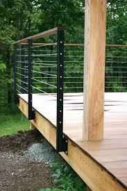 walk out basement modern cabin deck railing metal posts wire wood above walkout
