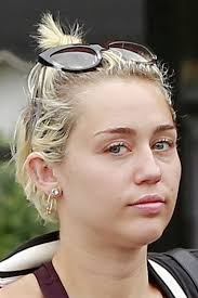 miley cyrus hairstyle name miley cyrus wavy golden blonde bun dark roots messy hairstyle