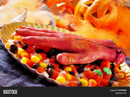 the background of halloween and amputated hand and a pile of halloween candies with scary