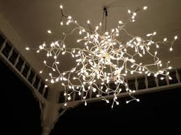 battery operated white christmas lights using an old umbrella form painted white and strung with white