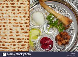 traditional seder plate matzo bread next to passover seder plate with the seventh symbolic