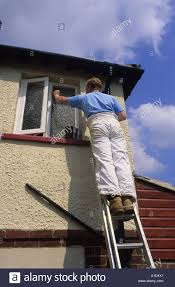 painter and decorator using ladder to paint exterior of house
