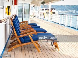 lounge chairs and beach umbrella on cruise ship deck stock photo