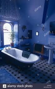 roll top bath below window in bright blue bathroom with black