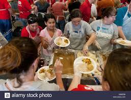 multi ethnic of volunteers help serve hundreds of free stock