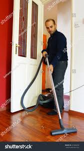 young man vacuuming living room stock photo 227648236 shutterstock