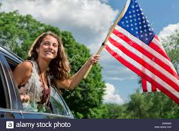 Car Window Flags Teenage Leaning Out Of Car Window Holding American Flag Stock