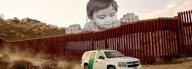 child curiously peeks over the us mexico border in jr installation