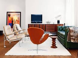 green and white leather sofa and orange chair on white fur rug