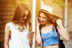 happy friends looking phone screen at sunset photo free