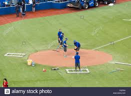 grounds crew prepares the home plate area for a baseball game at