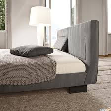 grey headboard connected by black cushion on grey bed and white