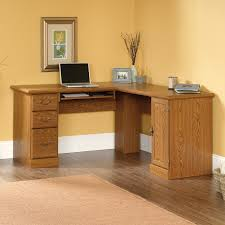 light brown wooden corner desk with triple drawers and storage