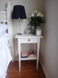 narrow wood bedside table lamp in the corner painted with white