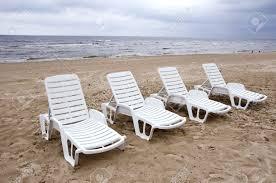 empty white plastic chairs near sea on beach sand stock photo