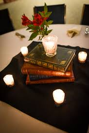 vintage book centerpieces with flowers and candles weddingbee