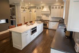 kitchen with black island and white cabinets white cabinets paired with countertops marble