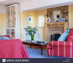 bright pink throw and striped armchair beside fireplace in yellow