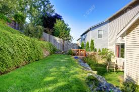 small green fenced back yard with retaining wall and two level