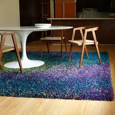 this peacock colored shag area rug contains purple blue and lime
