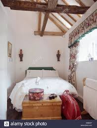 bed with white linen in white attic bedroom with large wooden