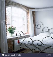 decorative wrought iron bed with white linen in simple white
