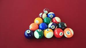 billiards closeup of colored pool balls rolling on green