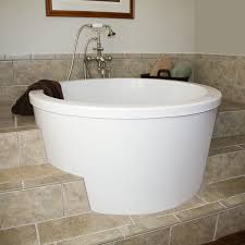 bathroom white round japanese soaking tub with tile flooring and