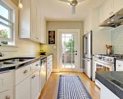 galley kitchen with white cabinets and rug runner make a galley