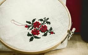 embroidery cross stitch flower ornament on a white fabric