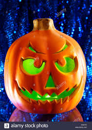 halloween themed background pumpkin lit from interior with glowing green light and shimmering