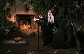 halloween witch with her magic book casting a spell stock photo