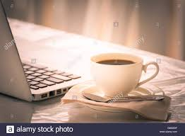 coffee cup tea pot cookies and laptop on wooden desk on cofe