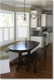 table with bench seat built in kitchen table under window and the kitchen is by
