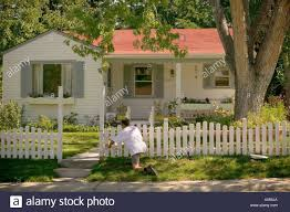Painting Of House by Man Painting White Picket Fence In Front Of House Stock Photo
