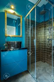 blue fashionable bathroom with golden tiles in shower stock photo