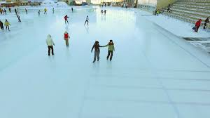 aerial view of ice skating two women friends outdoor ice rink