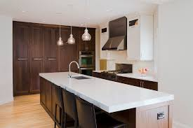 dark brown wooden kitchen cabinets and island having white