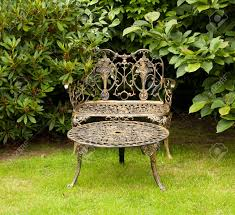 Vintage Cast Iron Patio Furniture - old fashioned gold colored cast iron table and bench on formal