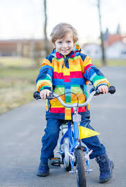 raincoat for bike riders kid boy in safety helmet and colorful raincoat riding bike stock