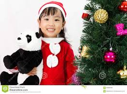 asian chinese little holding panda doll posing with christm