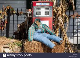 headless halloween a headless scarecrow sitting on a bale of hay in front of a