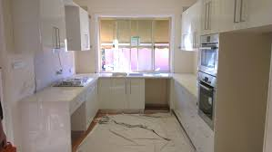 modern kitchen u shape design with white cabinetry also wall