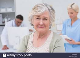 Doctor And Nurse Unhappy Patient With Doctor And Nurse Working In Background Stock