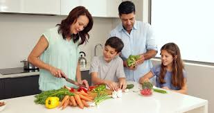 mother showing children how to chop vegetables at home in kitchen