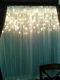 hang icicle lights behind a window sheer looks pretty from the