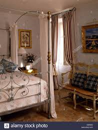 antique wrought metal bed with white drapes in french country