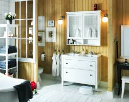 a white small bathroom with two white high cabinets a mirror and a