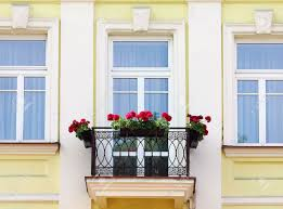 three house windows and balcony with flowers stock photo picture