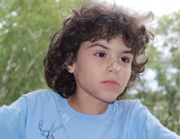 long front hair boys cute little boy with curly hair is posing in front of camera stock